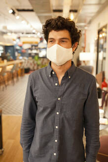 Serious young male employee in casual outfit and protective mask looking away while standing against blurred interior of modern coworking space - ADSF17838
