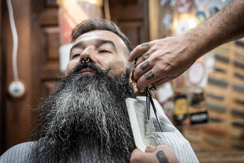 Professional tattooed barber in protective mask with comb and scissors cutting long beard of middle aged gray haired male customer while working in barbershop with vintage interior - ADSF17850