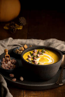 Nutritious pumpkin soup in bowl served on tray with crispy bread croutons and nuts on wooden table - ADSF18060
