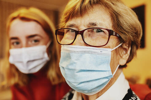 Grandmother wearing face mask and eyeglasses staring while sitting by granddaughter at home - JATF01296