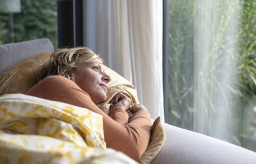 Mature woman looking through window while lying on sofa at home - BFRF02308