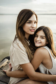 Daughter embracing mother while sitting at jetty - RCPF00341