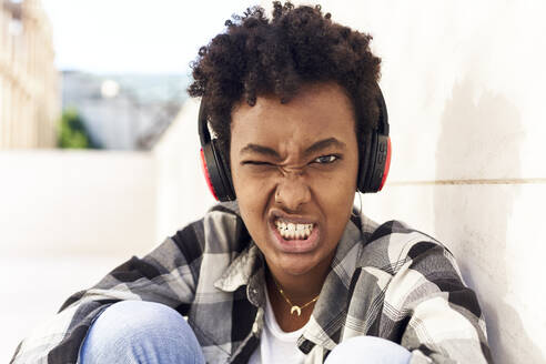 Afro young woman with grimace on face listening music by wall - VEGF03144