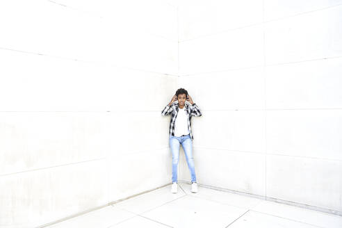 Young female hipster listening music through headphones while leaning against white wall - VEGF03153