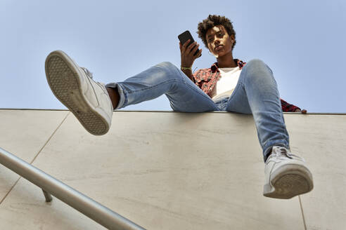 Young female hipster using smart phone while sitting on retaining wall against blue sky - VEGF03207