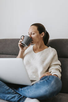 Woman drinking coffee while using laptop at home - DMGF00323