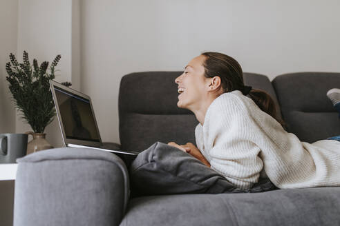 Woman laughing while talking to friend through video call on laptop at home - DMGF00329