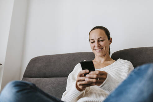 Smiling woman using phone on sofa at home - DMGF00335