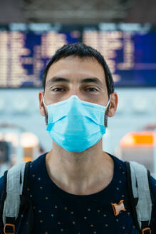 Portrait of a young man wearing a face mask on the airport - CAVF91204