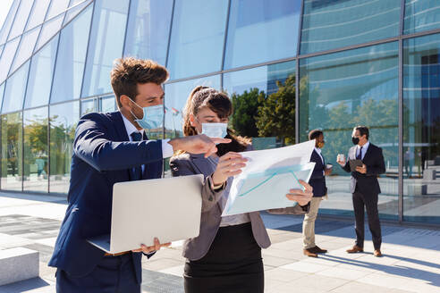 Unrecognizable young man and woman in formal suits and medical masks examining documents while working together on street using laptop near modern business building - ADSF18078