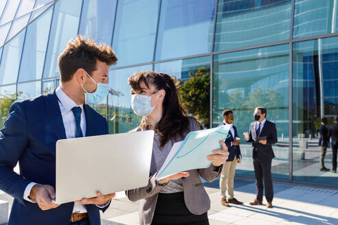 Unrecognizable young man and woman in formal suits and medical masks examining documents while working together on street using laptop near modern business building - ADSF18081