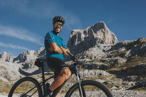 Smiling mountain cyclist with arms crossed at Picos de Europa National Park Cantabria, Spain - DMGF00354