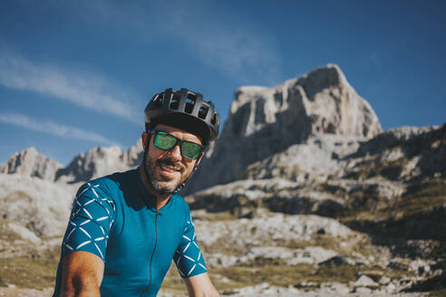 Smiling mid adult male cyclist wearing cycling helmet and sunglasses at Picos de Europa National Park, Cantabria, Spain - DMGF00357