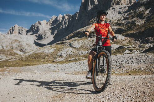 Woman with mountain bike at Picos de Europa National Park on sunny day, Cantabria, Spain - DMGF00366