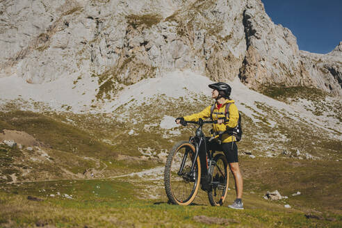 Woman with bicycle looking away against rock mountain on sunny day, Picos de Europa National Park, Cantabria, Spain - DMGF00375