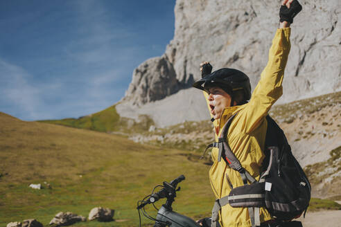Excited female cyclist with arms raised shouting at Picos de Europa National Park on sunny day, Cantabria, Spain - DMGF00378