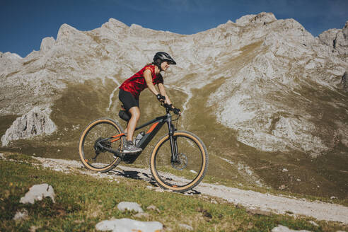 Female cyclist riding bike near rock mountain at Picos de Europa National Park, Cantabria, Spain - DMGF00381