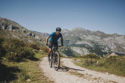 Male cyclist riding mountain bike on trail against sky, Picos de Europa National Park, Asturias, Spain - DMGF00384