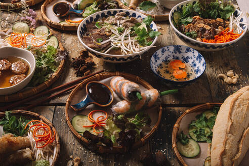 From above of assorted dishes of Vietnamese cuisine arranged on wooden table in luxury restaurant - ADSF18210