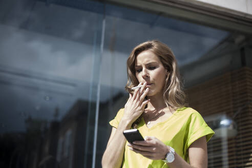 Young female entrepreneur using smart phone while smoking against office building on sunny day - AJOF00688