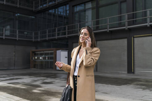 Smiling businesswoman talking on phone against office building - MTBF00721