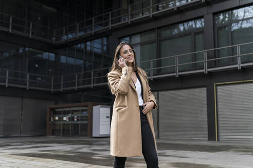 Smiling young female professional talking on phone while walking against office building - MTBF00724