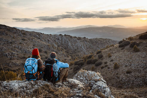 Male and female hikers enjoying sunset while sitting on rock mountain during vacation - RCPF00420