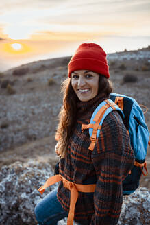 Happy female hiker with backpack standing on mountain during sunset - RCPF00423