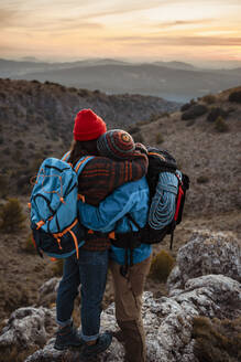 Couple embracing while standing on mountain peak during sunset - RCPF00435