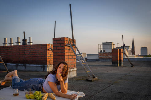 Brunette woman eating fruits, having a rooftop picnic at sunset sunset - NGF00719