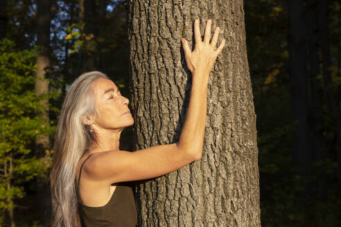 Woman with eyes closed hugging tree at park - FCF01929