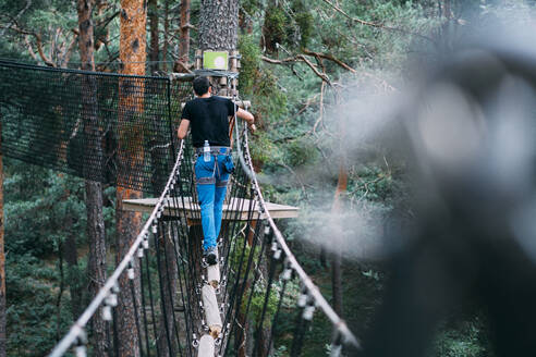 Young man crossing rope bridge in adventure park - ABAYF00037