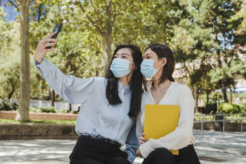 Unrecognizable young Asian female managers in classy clothes and medical masks relaxing in green park and taking selfie on smartphone - ADSF18354