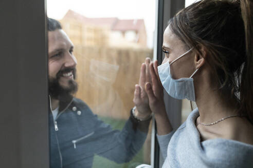 Couple touching hands from window glass during COVID-19 outbreak - WPEF03734