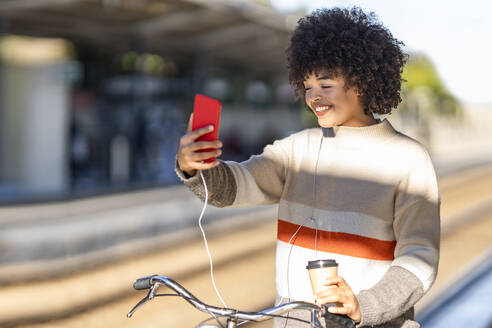 Young woman taking selfie while standing with bicycle and reusable cup at railroad station - GGGF00222