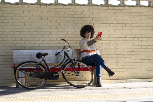 Smiling woman taking selfie while sitting on bench by bicycle against brick wall - GGGF00243