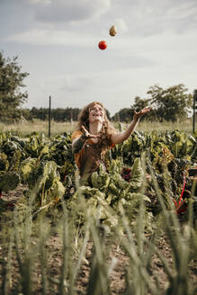 Playful farm worker playing with vegetable while harvesting crop at farm - MJRF00318