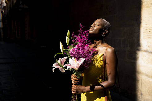 Female hipster with eyes closed holding flower bouquet on sunny day - RCPF00450