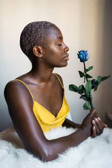 Woman with eyes closed holding blue rose against wall at home - RCPF00462