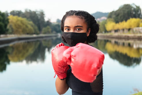 Serious young African American female boxer in protective mask and red gloves punching during workout on lake shore in park - ADSF18399