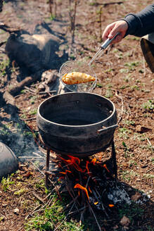Unrecognizable cook preparing delicious pasty in boiling oil in pot on camping fire in countryside - ADSF18408