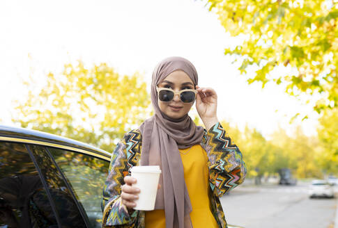 Woman with coffee cup wearing sunglasses while standing by car - JCCMF00049