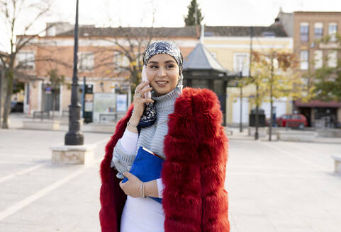 Young woman wearing fur coat talking on mobile phone while standing in city - JCCMF00055