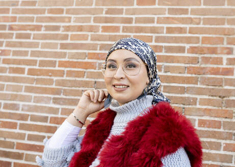 Woman wearing fur coat and eyeglasses looking away while standing against brick wall - JCCMF00061