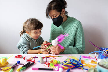 Grandmother and granddaughter making creative toys from pipe cleaners and pom-pom during COVID-19 - GEMF04432