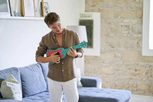 Male musician playing ukulele while standing in living room at home - KIJF03417