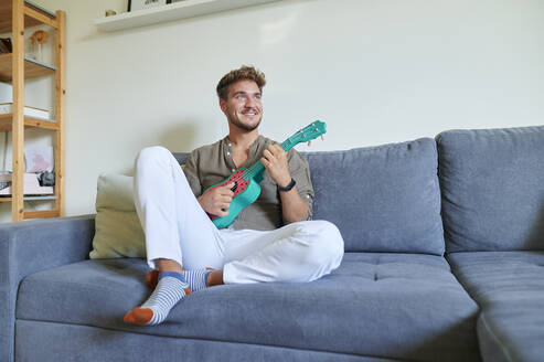 Smiling male musician playing ukulele while sitting on sofa at home - KIJF03420