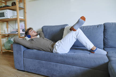 Young man with headphones listening music while lying on sofa at home - KIJF03423