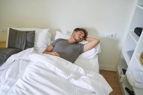 Man sleeping on bed in bedroom at home - KIJF03426