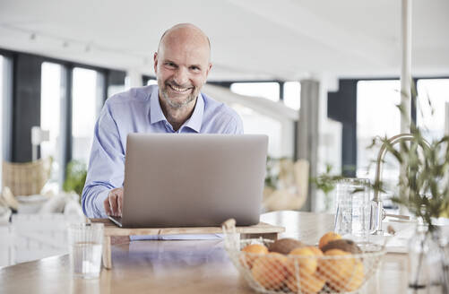 Smiling businessman using laptop while standing at home - FMKF06794